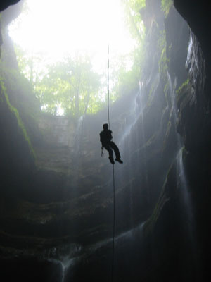 Student climbing rope in cave